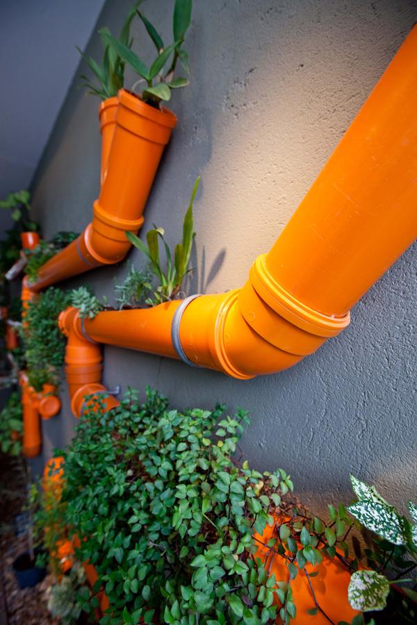 Трубы ярко-оранжевого цвета с растениями - необычная композиция способная преобразить интерьер