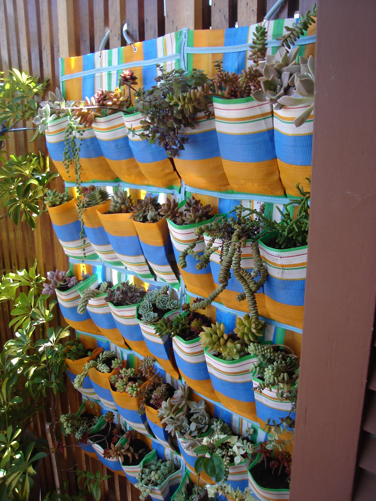 Текстильными полосатыми кармашками с разнообразными растениями можно дополнить любою вертикальную плоскость